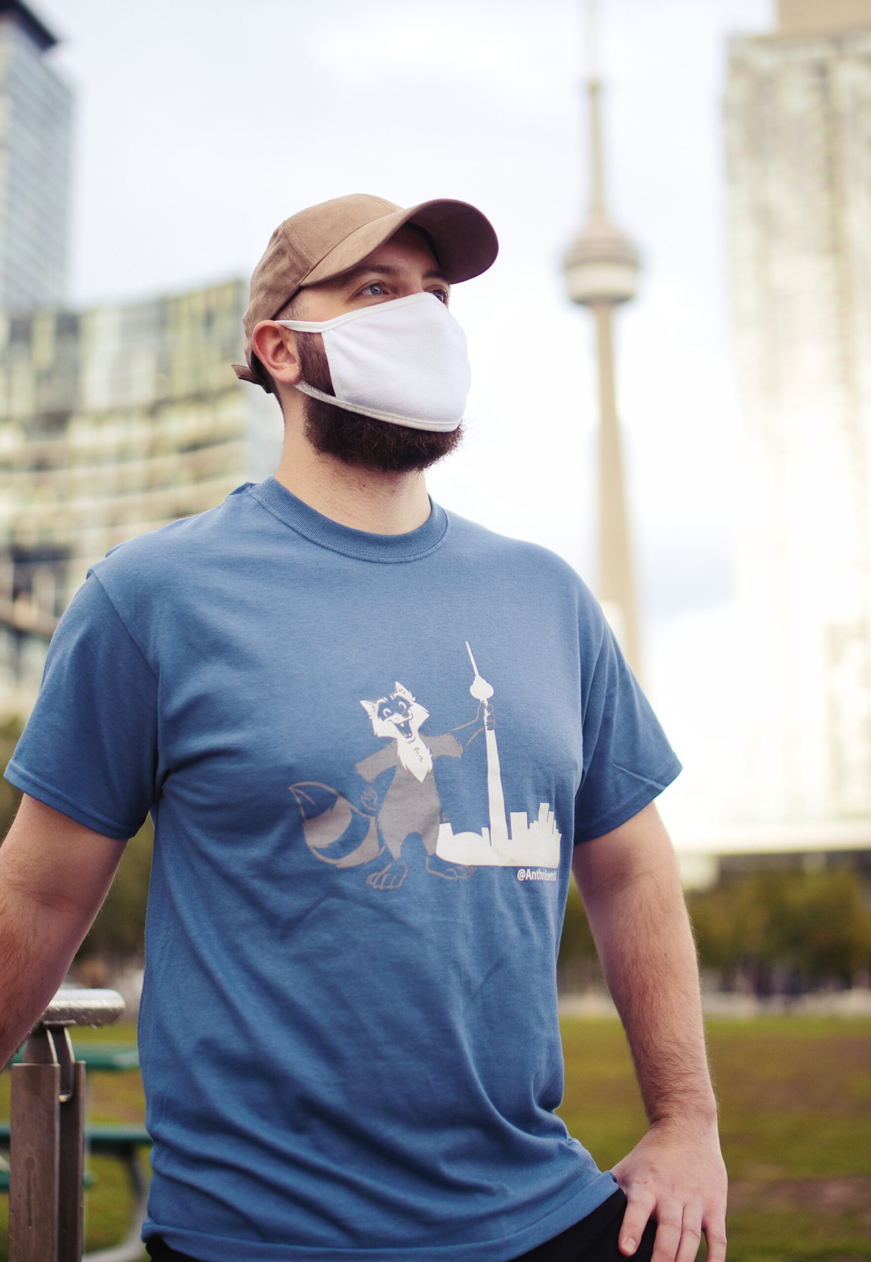Strong man in from of the CN tower, wearing a blue shirt with a racoon in front of the Toronto Skyline with the AEO logo.