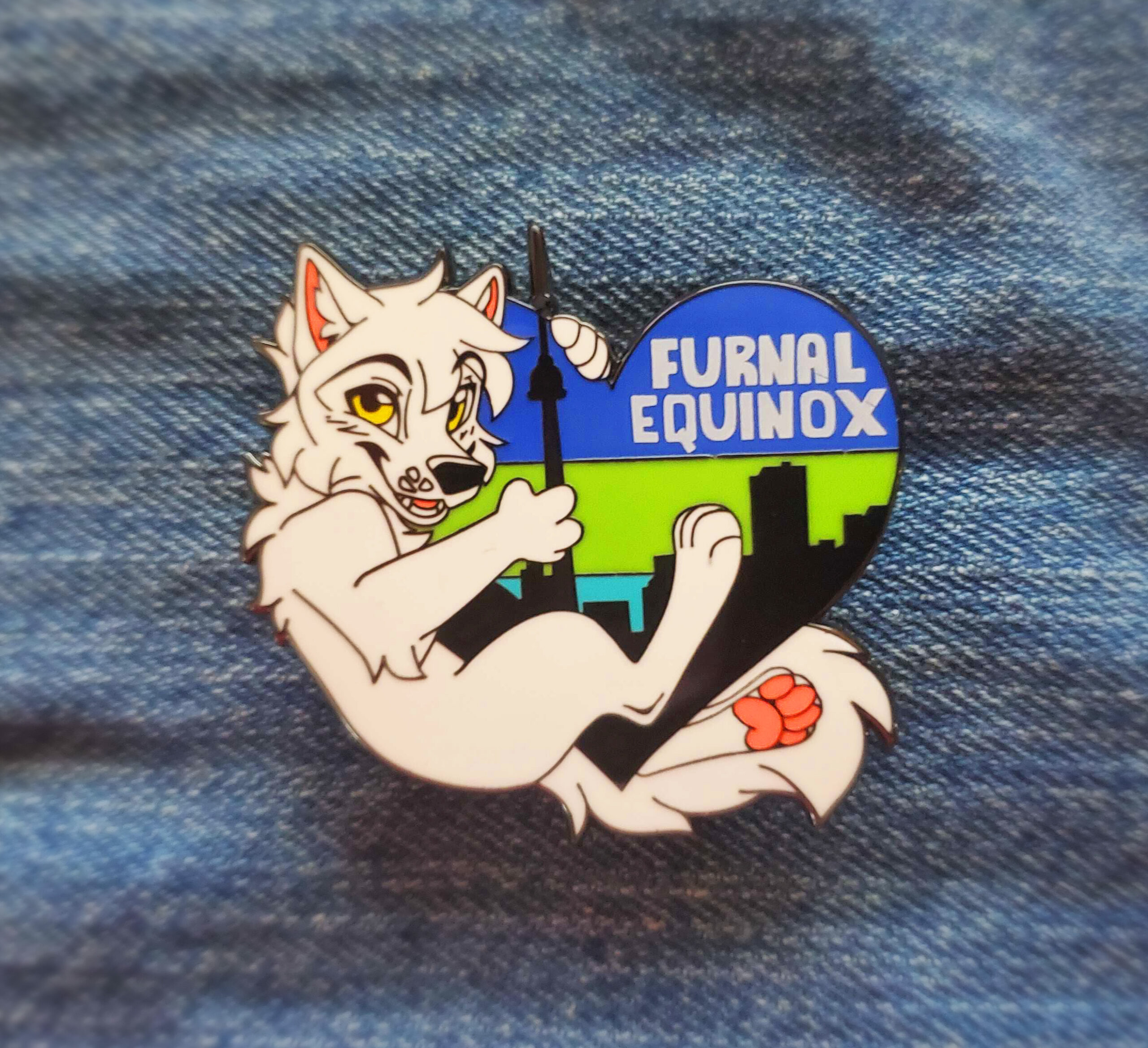 A close up of a hand holding the hard enamel pin. it's  that features a lynx riding a skateboard with the inscription FE 2020.